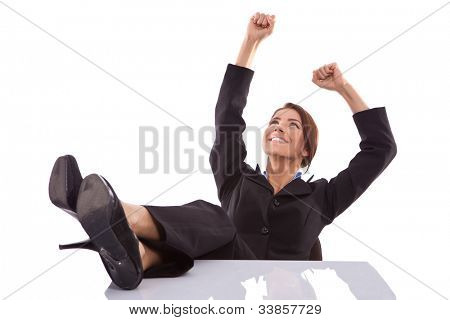 relaxed and winning business woman sitting with her legs on desk and hands in the air