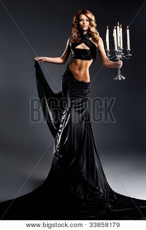 Fashion shoot of beautiful woman in a long dress over dark background