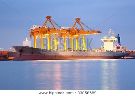 Big Container Cargo freight ship with working crane in shipyard at dusk for Logistic Import Export background