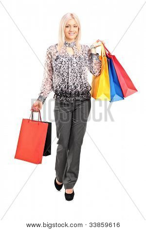 Full length portrait of a blond female walking with shopping bags isolated against white background