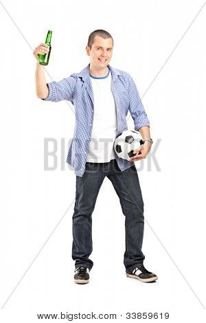 Full length portrait of an euphoric male fan holding a football and beer bottle isolated on white background