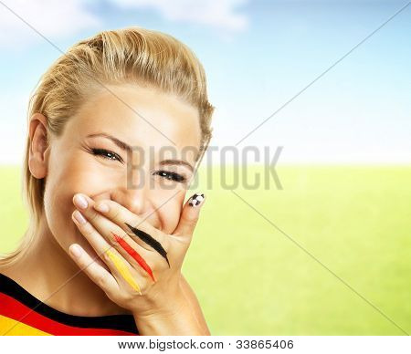 Smiling football fan, closeup on face, female covering mouth with painted in flag colors hand, woman expressing emotions of joy, German team supporter, girl watching game, outdoor field stadium