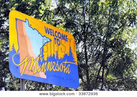 Low-angle view of a sign welcoming to the state of Minnesota with a leafy background