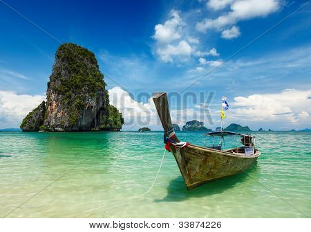Long tail boat on tropical beach (Pranang beach) and rock, Krabi, Thailand