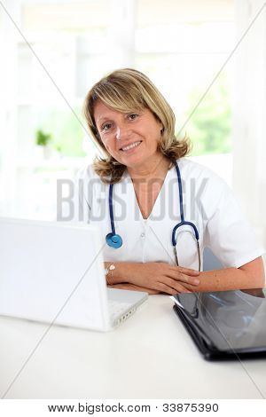 Portrait of mature nurse sitting at her desk