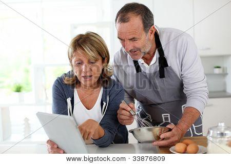 Sênior casal se divertindo na cozinha de casa