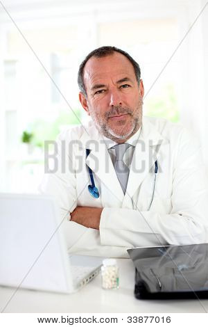 Portrait of mature doctor in uniform