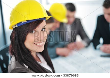 Business people in office wearing hard hat
