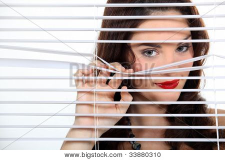 pretty woman behind blinds spying upon neighbours