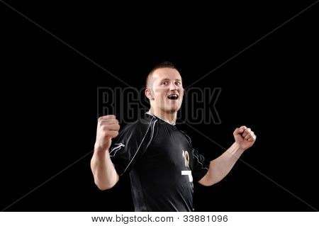 Happy soccer player is celebrating in dark