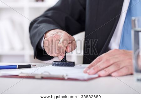 Man�¢�?�?s hand stamping documents, close-up