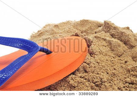 a pair of orange flip-flops on the sand on a white background