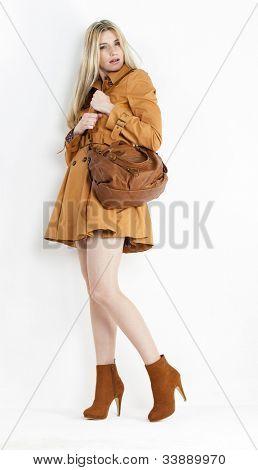mujer de pie con capa y moda zapatos marrones con un bolso de mano