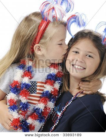 A pretty preschool girl kissing her elementary sister.  Both are dressed for Independence Day Celebrations.  On a white background.