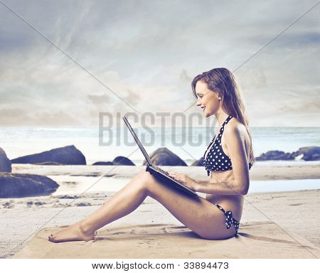 Beautiful woman sitting on a beach and using a laptop