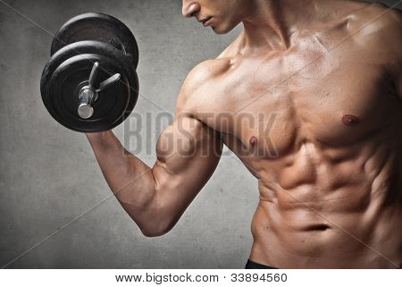 Brawny bare-chested young man lifting weights