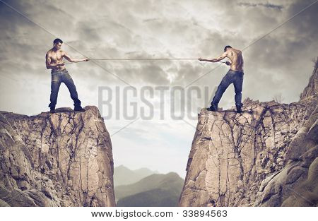 Two young men playing tug of war over a precipice