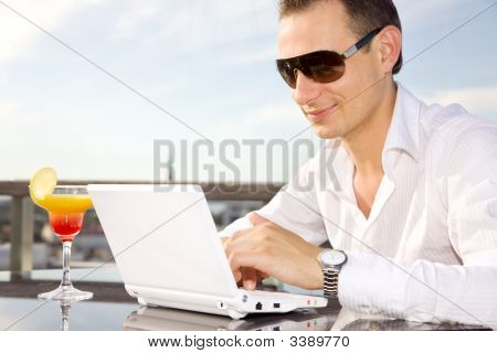 Businessman On Leisure With Laptop And Cocktail