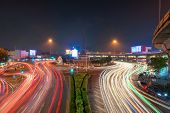 Victory Monument With Car Light Trails On Street Road In Bangkok Downtown Skyline. Thailand. Financi poster