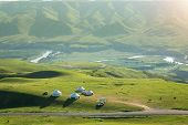 White Yurts On Pasture Field With Asphalt Road Crossing Through And Cattle Grazing,scenery Of Alpine poster