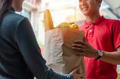 Food Delivery Service Man In Red Uniform Smiling Handing Fresh Food To Recipient And Young Woman Cus poster