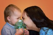 Mother With Baby Holding The Mask From The Nebulizer And Laugh. Treatment For Viral Colds. The Conce poster