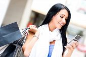 stock photo of mobile-phone  - Shopping woman sending a text message on her cell phone - JPG