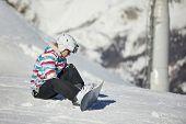 Snowboarder adjusting binding on her equipment poster