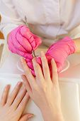 Medicine, Cosmetology And Manicure. Woman Manicure Master, In Pink Gloves Doing Manicure Client In T poster
