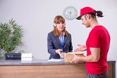 Young male courier delivering box to hotels reception poster
