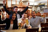 picture of watch  - Happy friends in pub watching sport in TV together drinking beer cheering for team and celebrating - JPG
