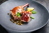 Traditional roasted Christmas duck breast and leg with orange slice and herbs as closeup on a modern poster