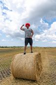 Strong Young Man In Red Wig Stands On The Round Haystack Among The Field And Shows His Biceps poster
