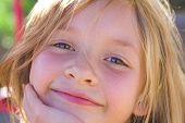 foto of 6 year old  - Six year old girl smiling with sunlight shining in her hair and playground equipment in the background