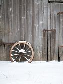 Old Wooden Barn Wall With An Old Wooden Cartwheel Standing In Front Of It. With Snow On Cartwheel An poster