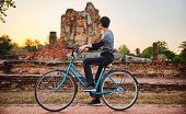 solo male thai tourist on bike visiting sukhothai historical park in thailand poster