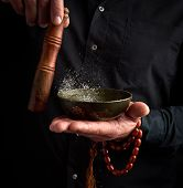 Adult Man In A Black Shirt Rotates A Wooden Stick Around A Copper Tibetan Bowl Of Water. Ritual Of M poster