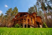 picture of house woods  - Big wooden mansion in pine forest - JPG