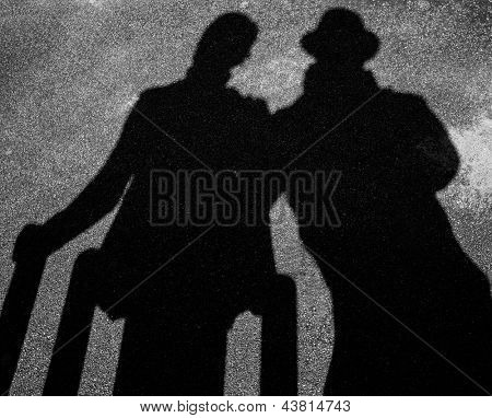 Two strangers shadows on pavement