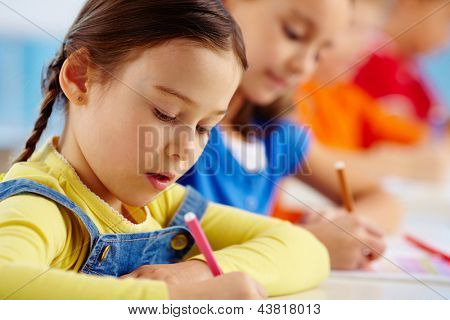 Portrait of lovely girl drawing at workplace with schoolmate on background