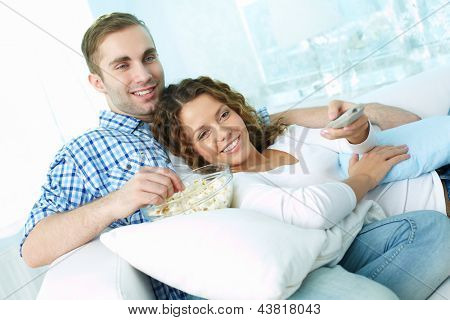 Young lovers enjoying lazy weekend watching TV and eating pop-corn