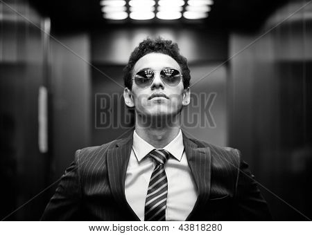 Black-and-white portrait of an ambitious business guy wearing sunglasses