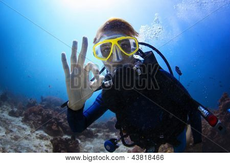 Underwater shoot of a woman diving with scuba and showing ok signal