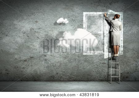 Businesswoman standing on ladder opening visional window