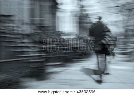 man walking on a city street in motion blur, brownstone buildings as a background, rear view