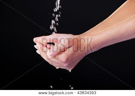 Water falling on female hands, over black background