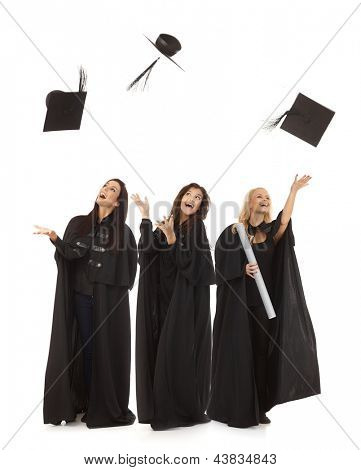 Three female graduates in academic dress throwing in the air square academic cap smiling happy.