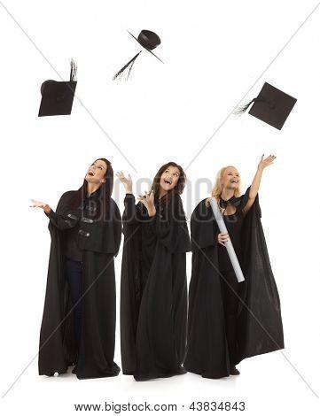 Three female graduates in academic dress throwing in the air square academic cap smiling happy.