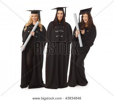 Three pretty female graduates in academic dress smiling happy, holding diploma.