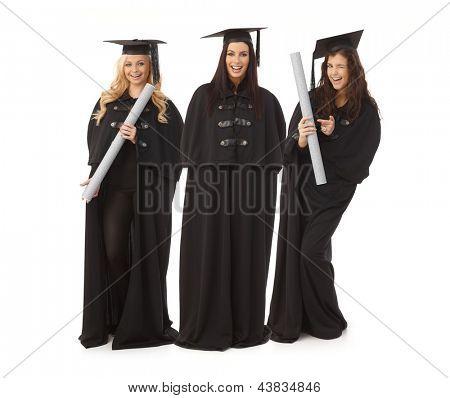 Three pretty female graduates in academic dress smiling happy, holding diploma.